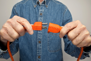 A man wearing a blue shirt plugging in an orange cord.