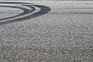A tire track on asphalt.