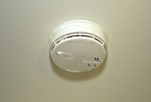 A carbon monoxide detector secured to a white ceiling.