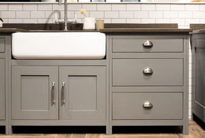 A gray kitchen cabinet with a white sink.