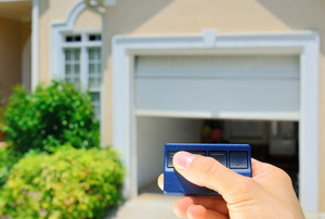 hand pushing remote to open or close garage door