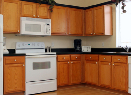refinished kitchen cabinets with white appliances