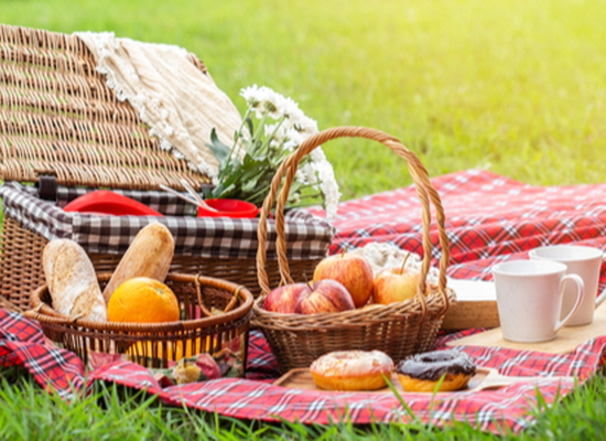 picnic basket and blanket laid out with fruit, donuts, mugs, and bread