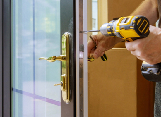 hands using drill to replace hardware in front door