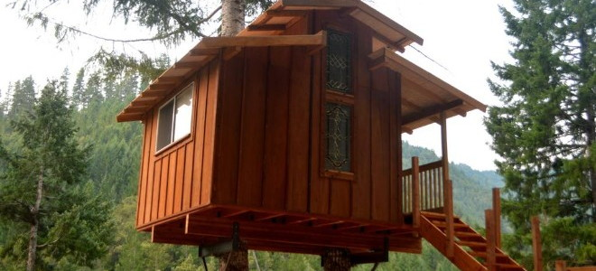 Basic square treehouse with multi-tiered roof and wooden stairs