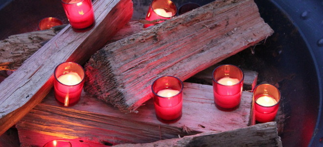 an unlit firepit with red candles on the logs