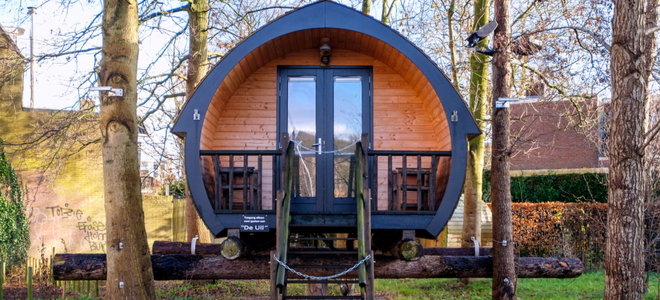a curved tiny house cabin elevated on logs