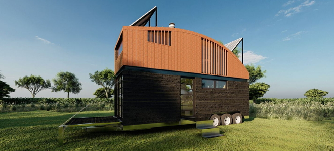 tall mobile home with curved roof and solar panels on a trailer