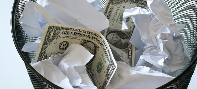 dollar bills and crumpled paper in a garbage can