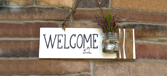 A rustic welcome sign hanging outside a home