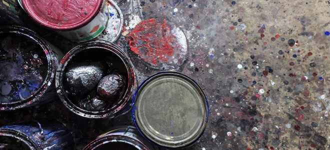 old paint cans on a speckled concrete floor