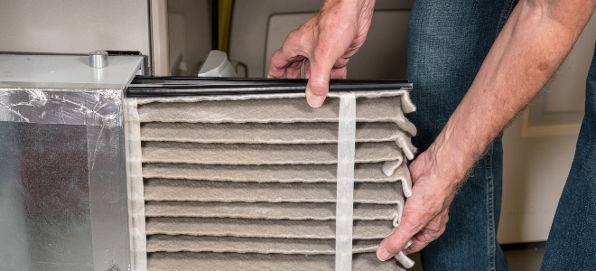 hands changing a furnace filter