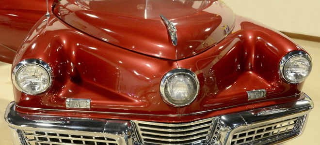 a classic red car with large chrome bumper and zig-zag hood
