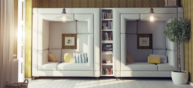White cushioned seats built into a wall with shelving in between them
