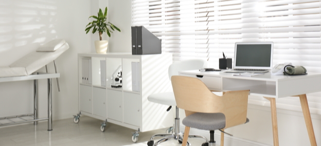 Office with modern white desk, organizational cubicle on wheels, and exam bed