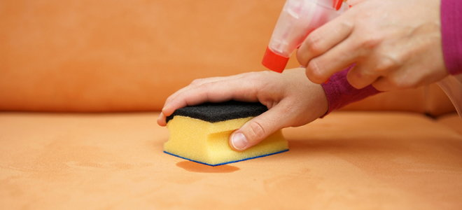 Someone cleaning a couch with a sponge and a spray bottle.