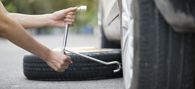 woman loosening lug nuts to change a tire