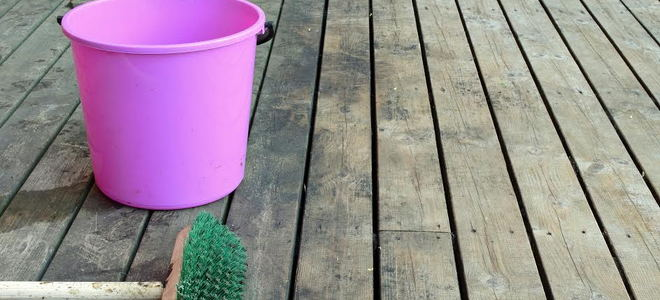 A pink bucket and a broom on a dirty wood deck.