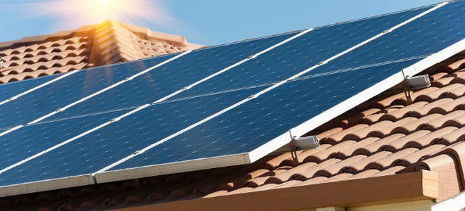 A Section Of Solar Panels On Red Tile Roof Against Blue Sky With