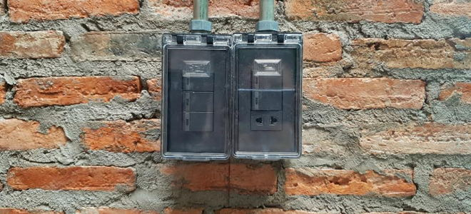 An electrical power box against a brick wall.