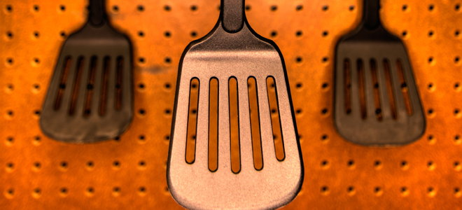 spatulas hanging on a pegboard organizer wall