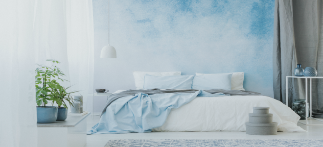 Сине-белая ombre стена в спальне за кроватью.