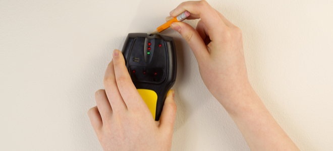 hands using a stud finder and making wall marks with pencil