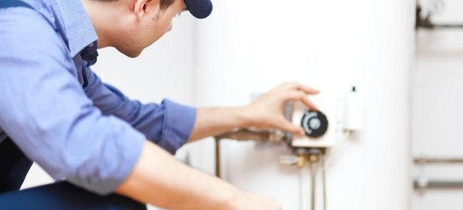 техник работает на водонагревательном баке