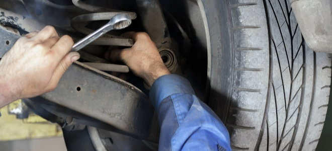 workers inspecting car suspension