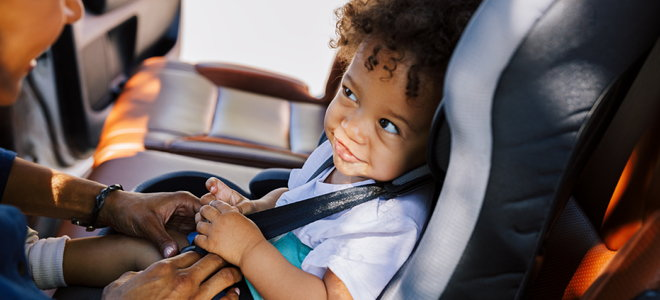 cute child smiling at a woman from their car seat
