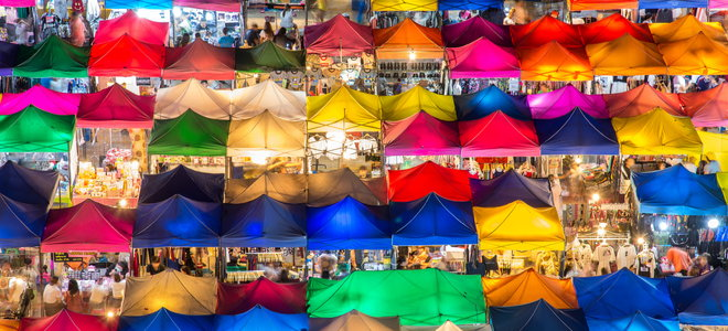 a busy flea market filled with colorful tents