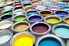 Rows of open paint cans in a variety of colors