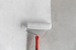 Paint roller applying white paint to wall