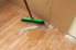 A broom sweeping up drywall dust.