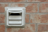 dryer vent on the side of a brick house
