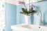 a small sink in a blue tiled bathroom with purple flowers