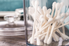 Cotton swabs in a jar on a countertop.
