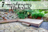 "A yard landscaped in wood, stone, and tile with the words, ""7 Hardscaping Materials."""