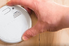 man uninstalls security alarm from home