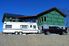 An trailer and a truck in front of a house under construction.