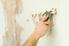 A man removes wallpaper.