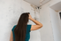 woman looking at mold in the corner of a room