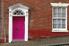 A pink door in a brick building.