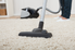 a woman vacuuming a cream colored area rug