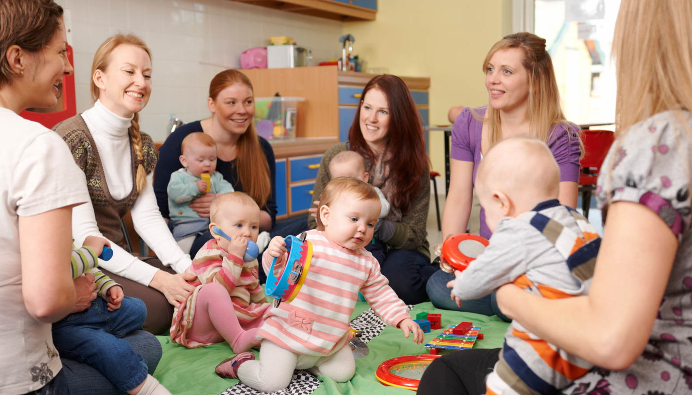 Mothers playing with babies in nursery