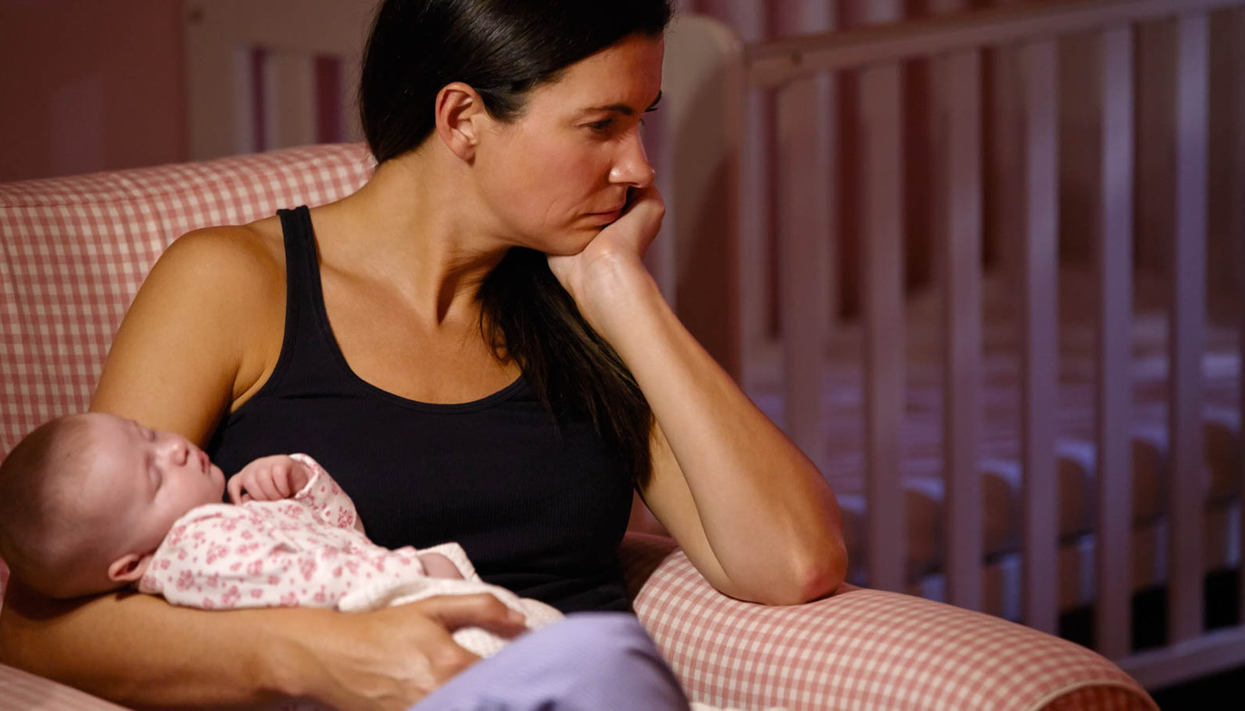 Depressed mother holding baby on couch