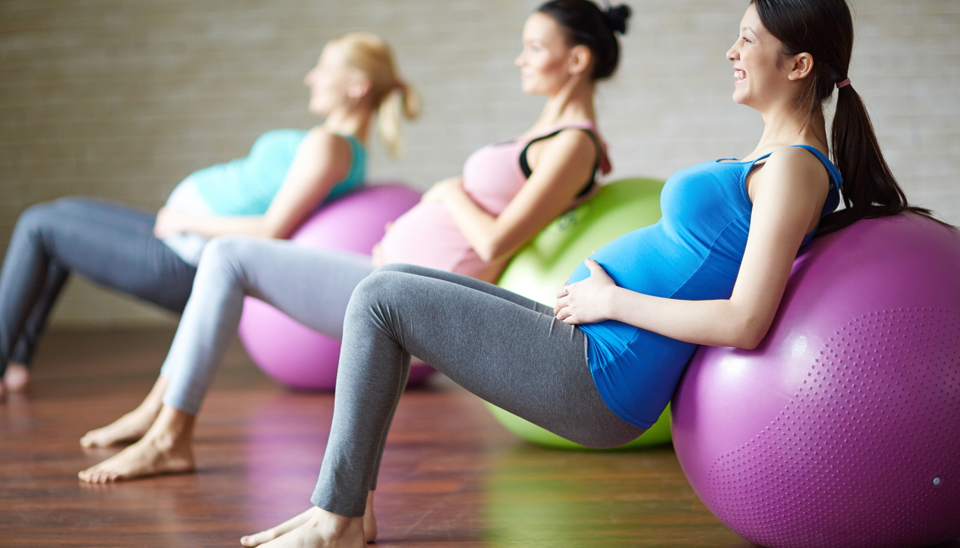 pregnant women stretching on exercise ball