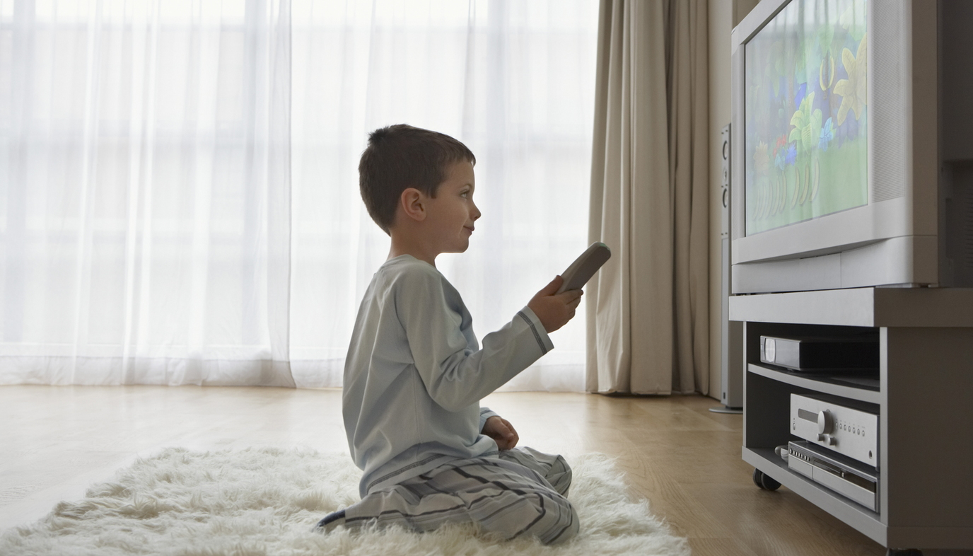 boy watching television at home alone