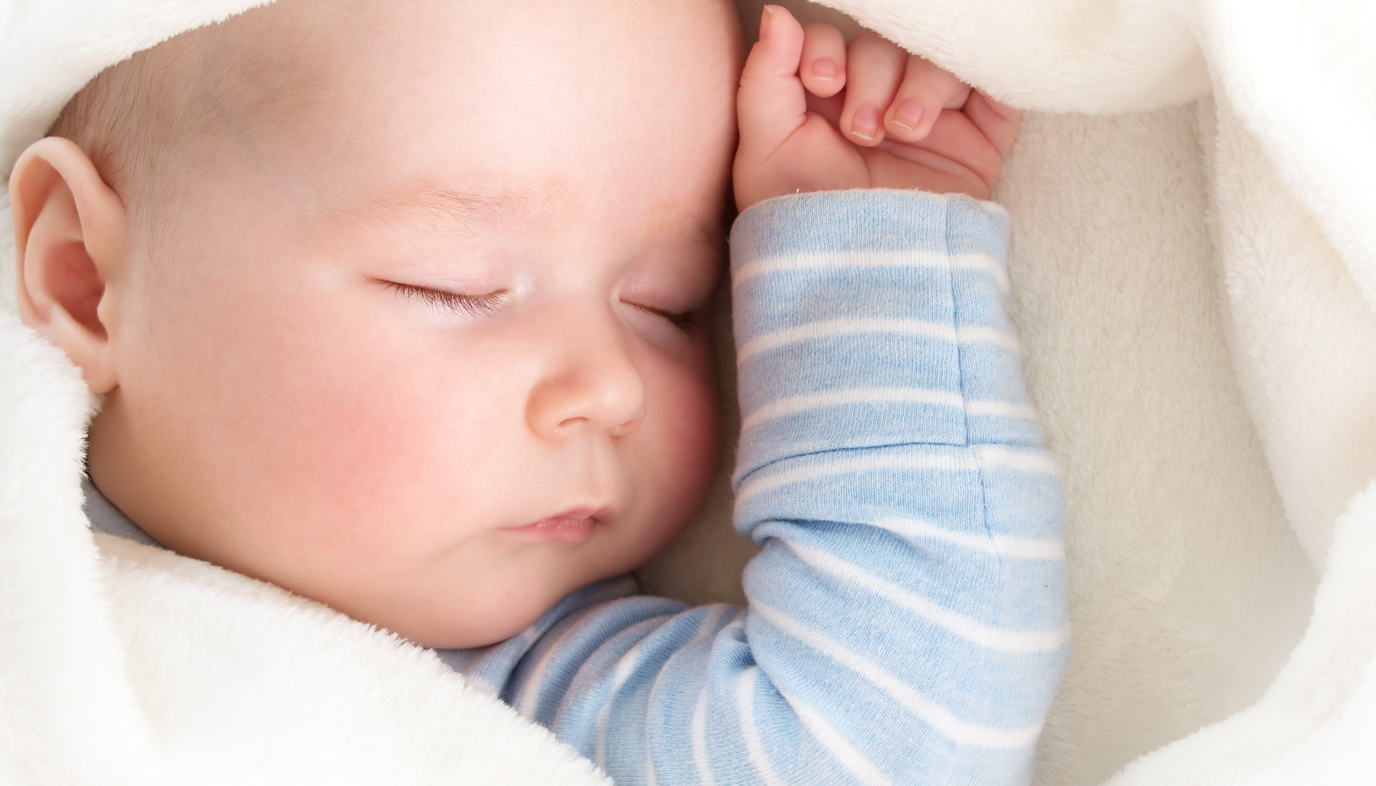 baby sleeping under blanket