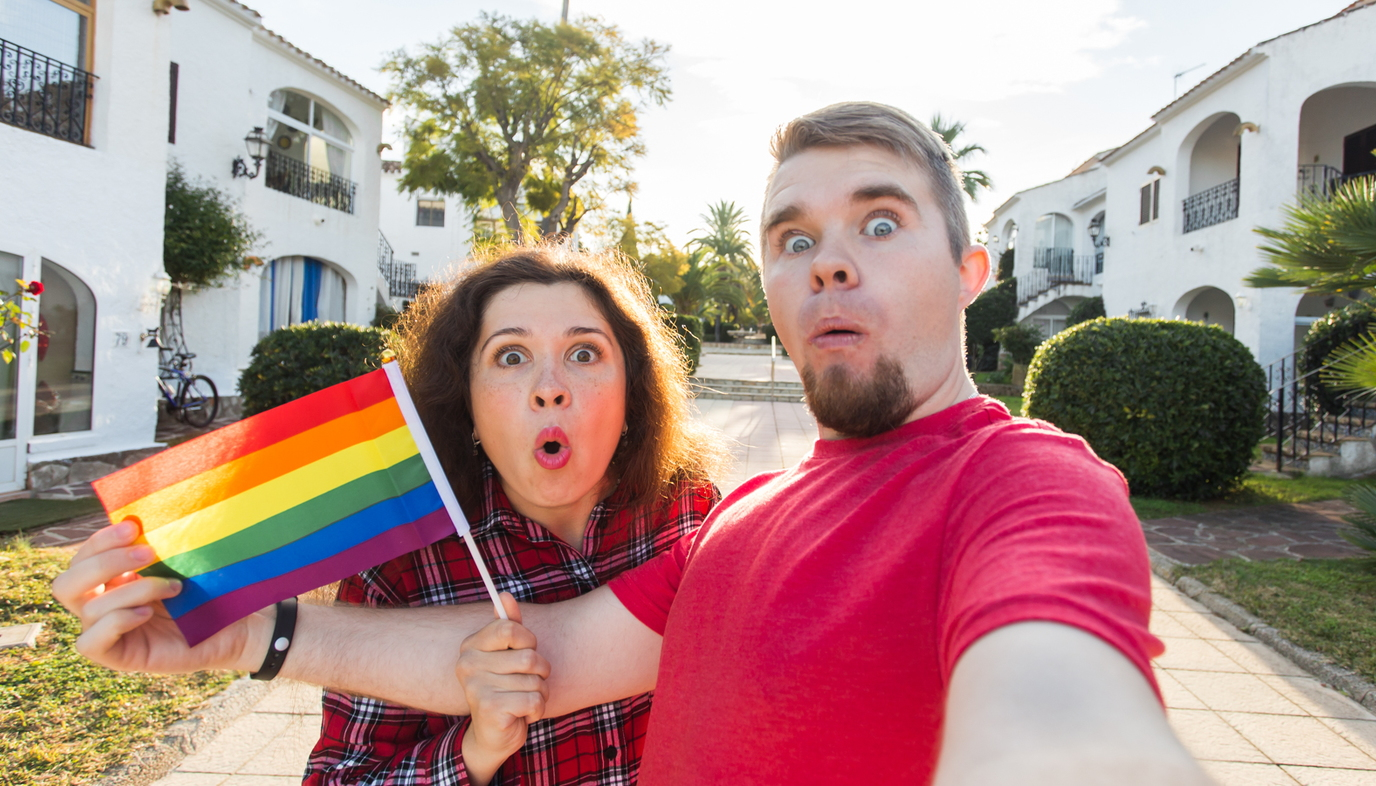man and woman holding rainbow flag